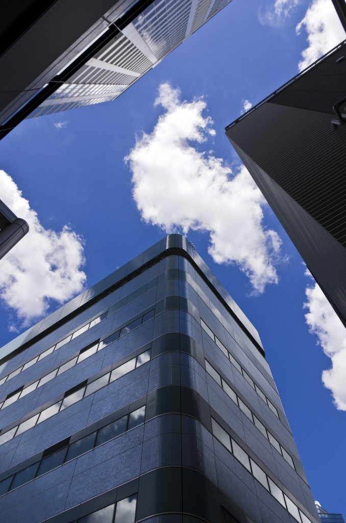 見上げたオフィスビルと青空